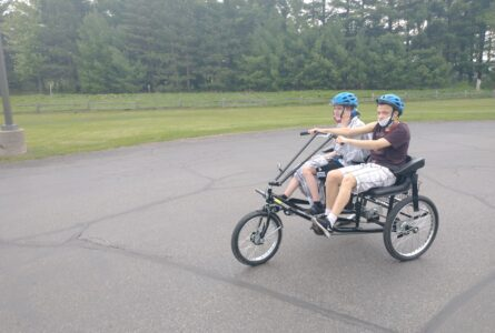 JESSICA SWAN PHOTO The Independent-Register Brodhead students Jesse Douglas and Jayden Hanson enjoy some time outside pedaling the new side-by-side tricycle that's specially adapted for students with special needs.  Grant money was used to purchase two tricycles.